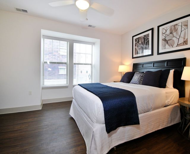 Orleans Landing - Bedroom with dark wood flooring, bright windows, and ceiling fans
